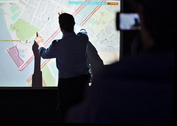 Zivilschützer zeigt etwas auf einem Bildschirm.