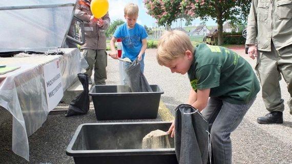 Kinder am Sandsack füllen