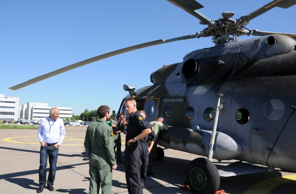 Mitglieder der verschiedenen Teams stehen vor dem Helikopter des tschechischen Teams und besprechen den Ablauf.