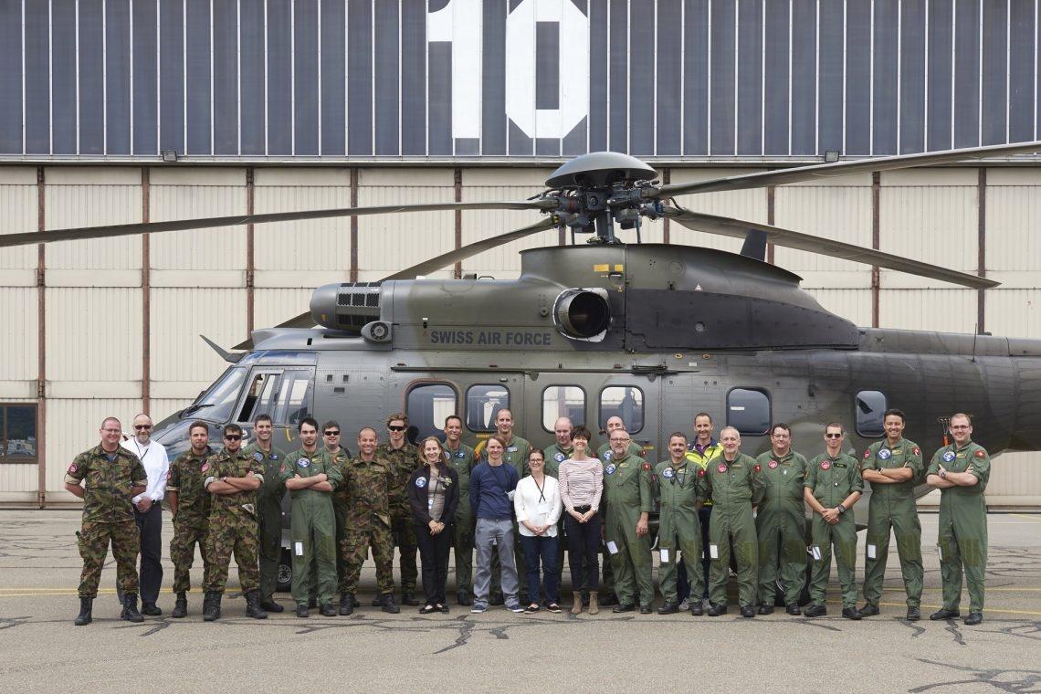 Gruppenbild der schweizerischen Messequipe vor ihrem Helikopter.