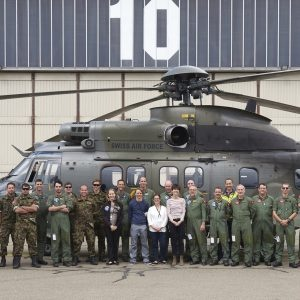 Group picture of the entire Swiss measure team in front of their helicopter.
