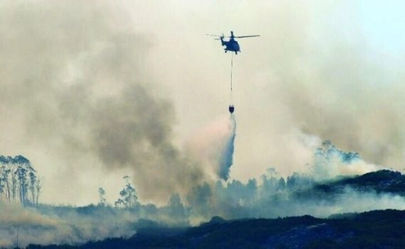 Un elicottero durante le operazioni di spegnimento di un incendio boschivo in Portogallo.
