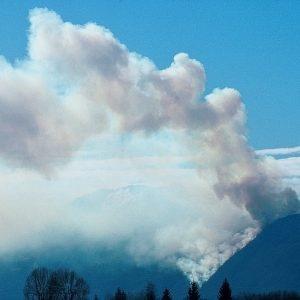Nell'immagine una colonna di fumo si erge sulle montagne sopra Ascona.