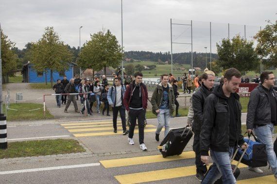Bild zeigt eine Gruppe Menschen mit Gepäck.