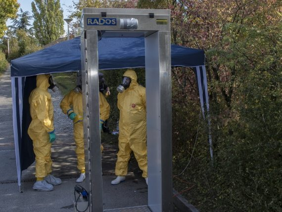 Bild zeigt Detektor für Radioaktivität und Menschen im Schutzanzug.