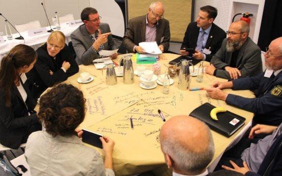 Das Bild zeigt Menschen an einem runden Tisch, die diskutieren.