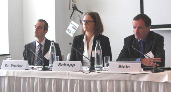 Das Bild zeigt drei Experten, die eine Podiumsdiskussion halten.