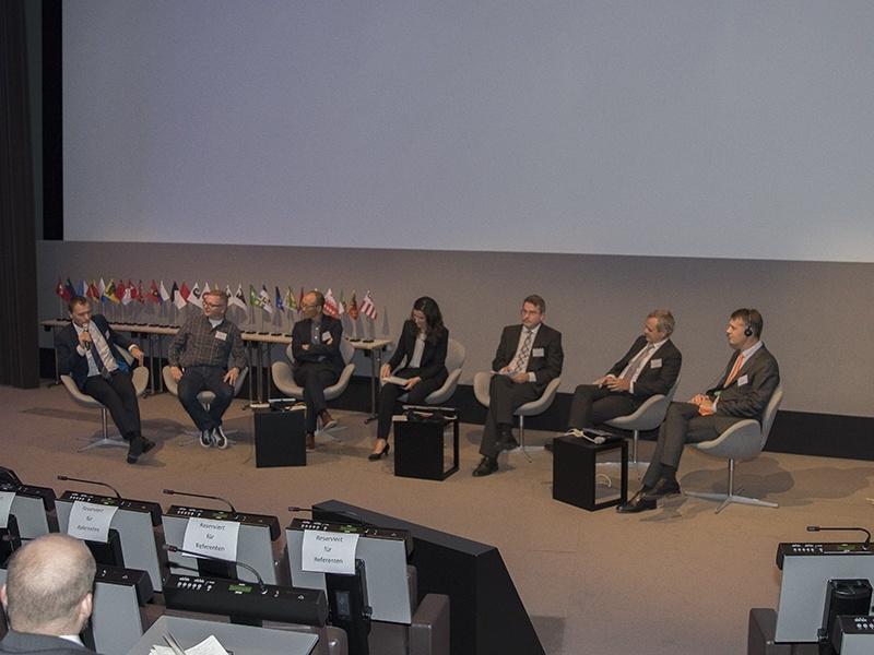 Foto zeigt Menschen, die auf einem Podium diskutieren.