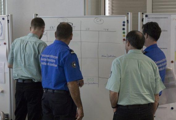 Zwei Einsatzleute des Grenzwachtkorps und zwei an der Übung teilnehmende Personen sehen sich Informationen auf einer Plakatwand an.