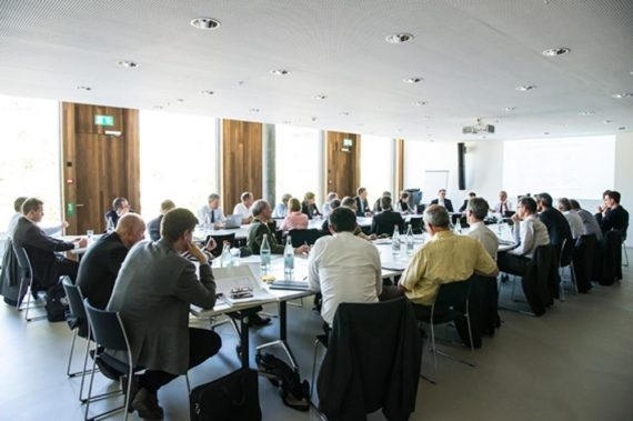 L'immagine mostra una sala conferenze affollata.