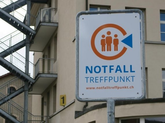 Nell'immagine, un cartello stradale indica verso un punto di raduno per le emergenze.