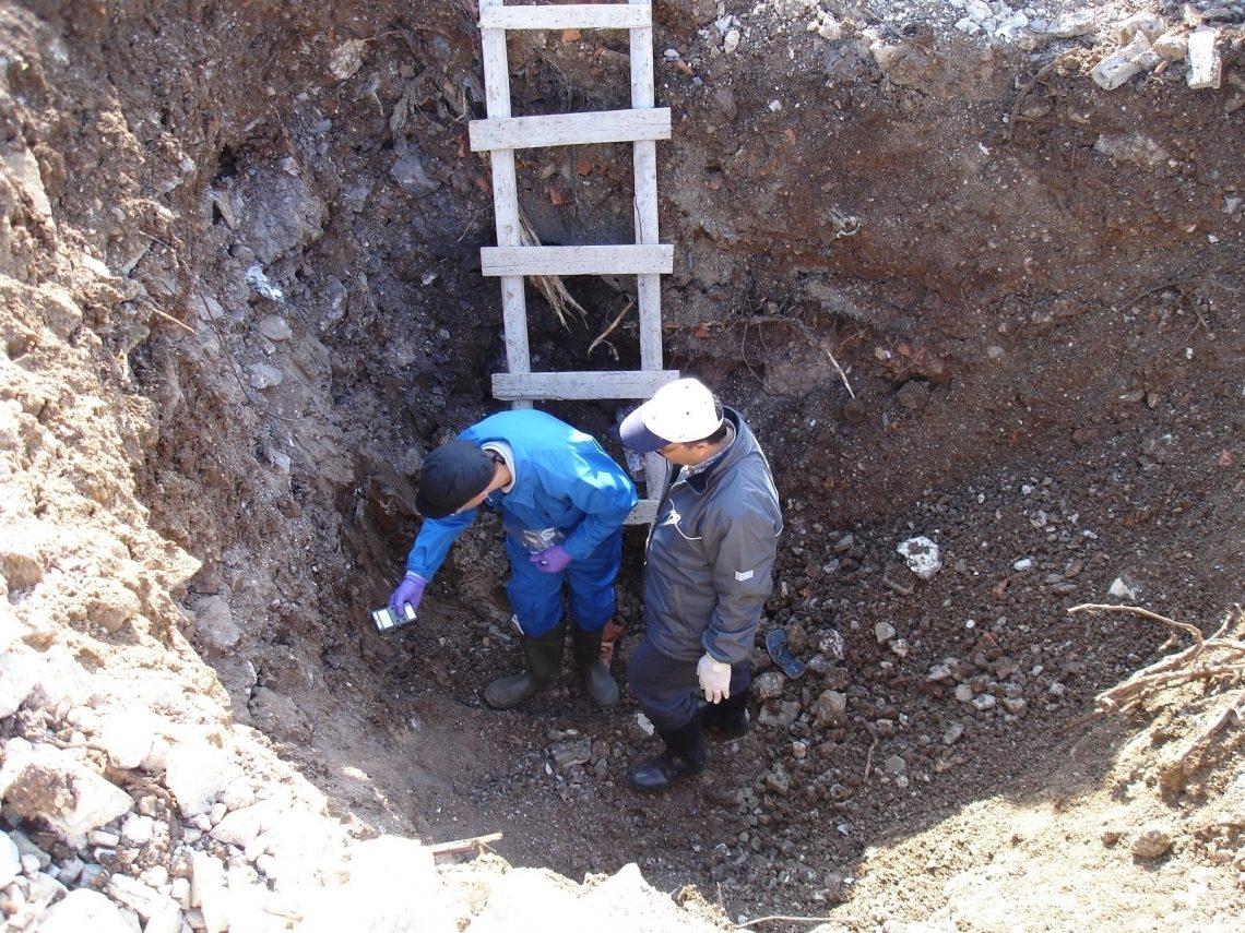 Un homme debout dans une fosse tient un compteur Geiger qu'il dirige contre la pente