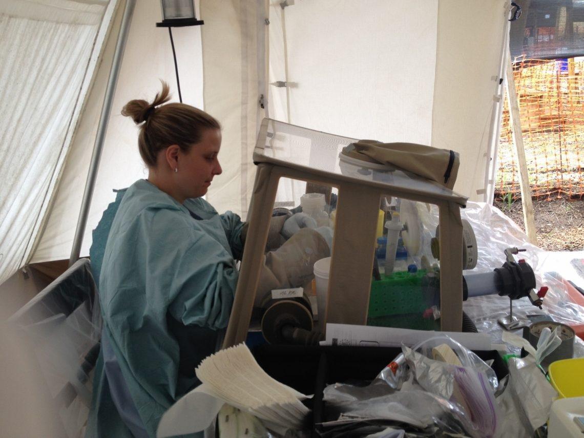 Una donna lavora alla scatola a guanti (glovebox).