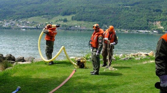 La figura mostra dei pionieri della PCi intenti a costruire argini contro l'esondazione sulle rive del Lago di Bienne