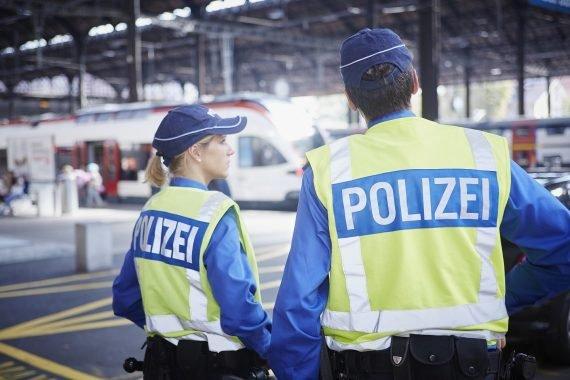 Zwei Polizisten stehen an einem Bahnhof und sprechen zusammen.