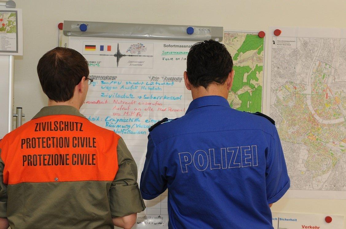 Ein Angehöriger des Zivilschutzes steht neben einem Polzisten