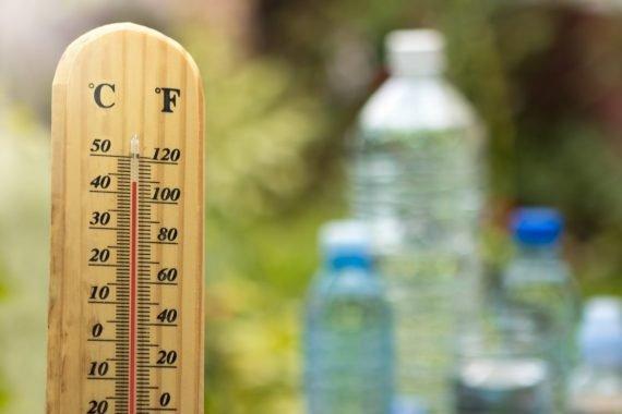 Ein Thermometer steht neben drei Wasserflaschen