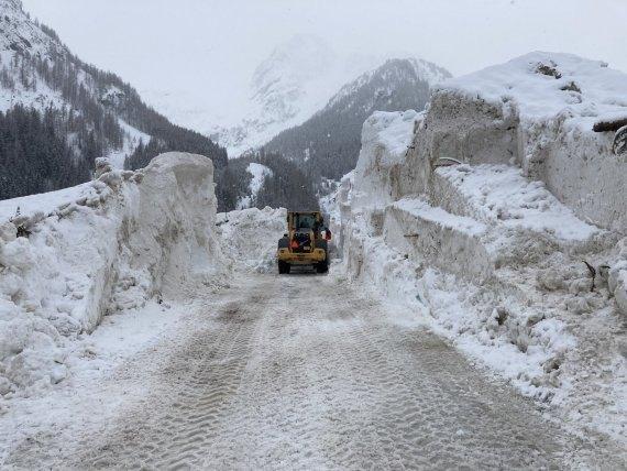 Un veicolo da cantiere sgombera la neve della valanga.