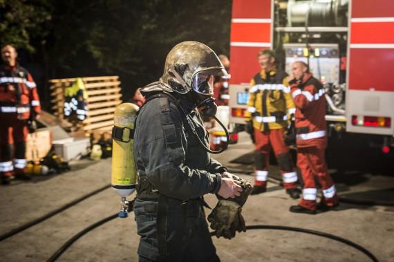 Ein Feuerwehrmann der Milizfeuerwehr Zürich zieht Sicherheitshandschuhe an.