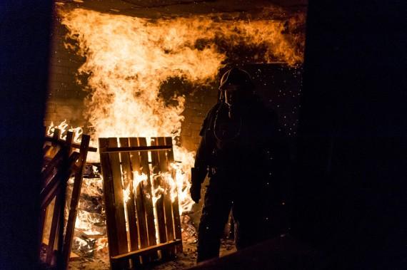 Ein Feuerwehrmann der Milizfeuerwehr Zürich steht neben dem Flammen des Feuers im Brandhaus.
