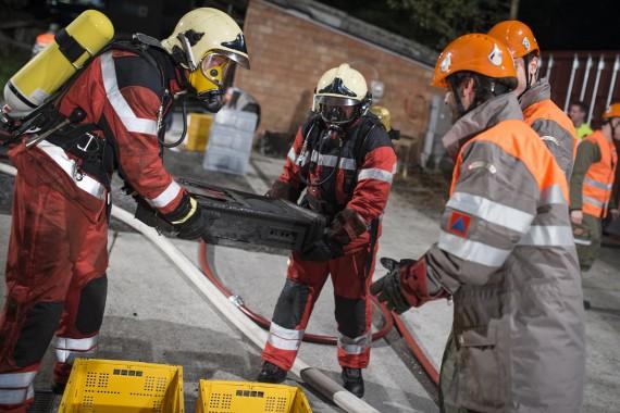 Feuerwehrleute der Milizfeuerwehr der Stadt Zürich übergeben die geborgenen Objekte an Angehörige der Kulturgüterschutzkompanie 50 des Zivilschutzes der Stadt Zürich.