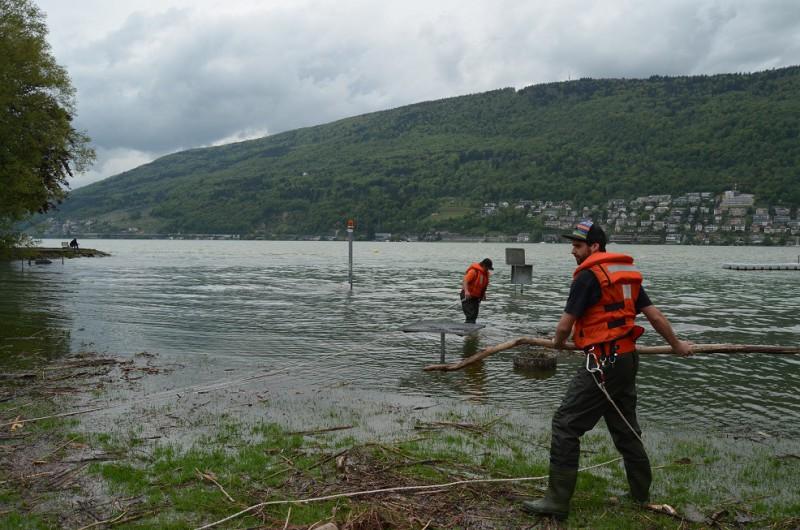 Die Zivilschützer der ZSO NIDAU sind beim Zusammentragen von Schwemmholz mit Seilen und Schwimmwesten gesichert.