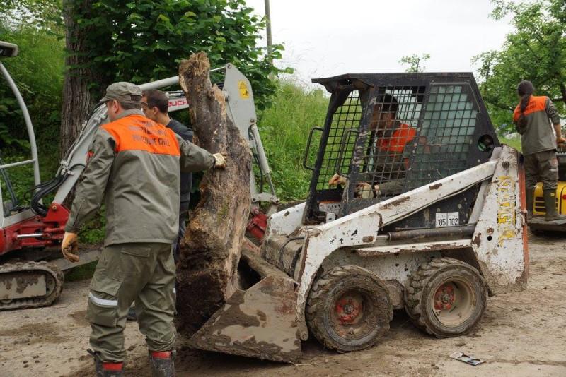 3 Zivilschützer entsorgen einen auf der Strasse liegenden Baumstamm mithilfe eines kleinen Baggers.