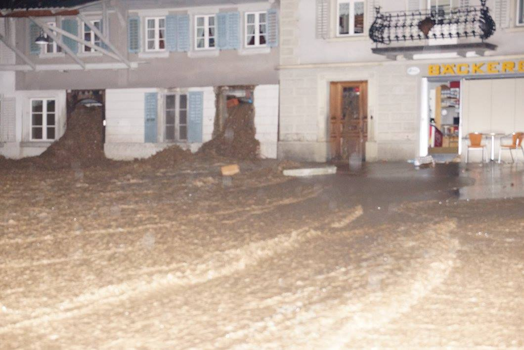 Die Bäckerei ist komplett mit Geröll und Wasser überflutet. Die Strasse vor der Bäckerei ist ebenfalls überflutet.
