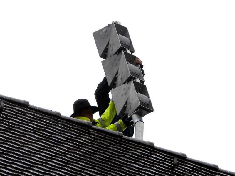 Deux personnes montent une sirène sur le toit d'une habitation.