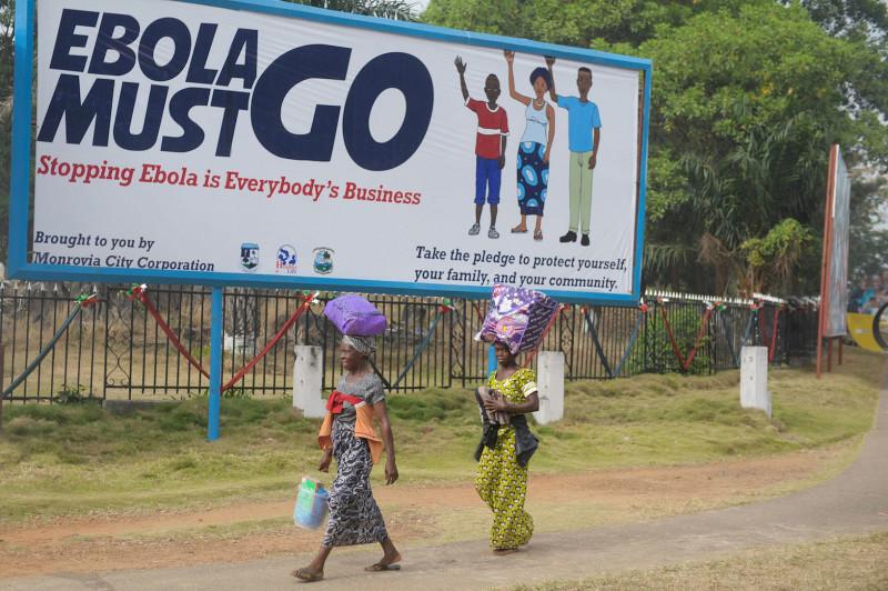 """Zwei Frauen in Monrovia, Liberien, gehen an einem Plakat vorbei, auf welchen steht: """"Ebola must go. Stopping Ebola is Everybody's Business."""""""
