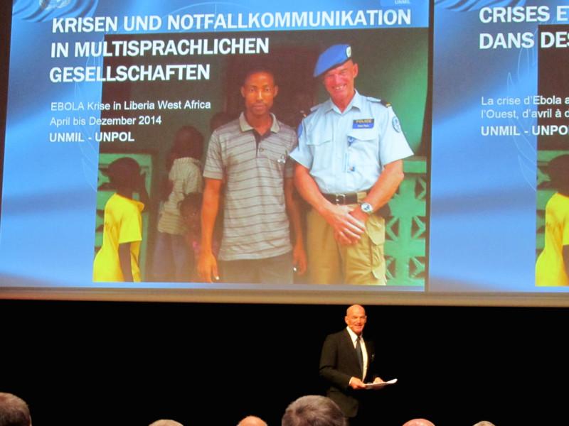 Felix Walz referiert an der Bevölkerungsschutzkonferenz 2015. Im Hintergrund seine Präsentation mit einem Foto, das ihn währen des Liberia Einsatzes zeigt.
