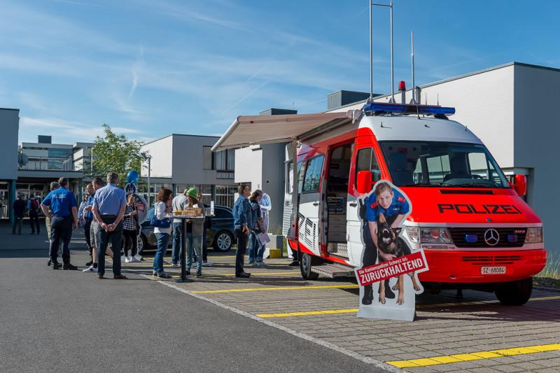 Das Bild zeigt einen Kastenwagen der Polizei. Daneben versammelt sind einige Polizisten und Besucher an Stehtischen. Diese tauschen sich bei Essen und Trinken aus.