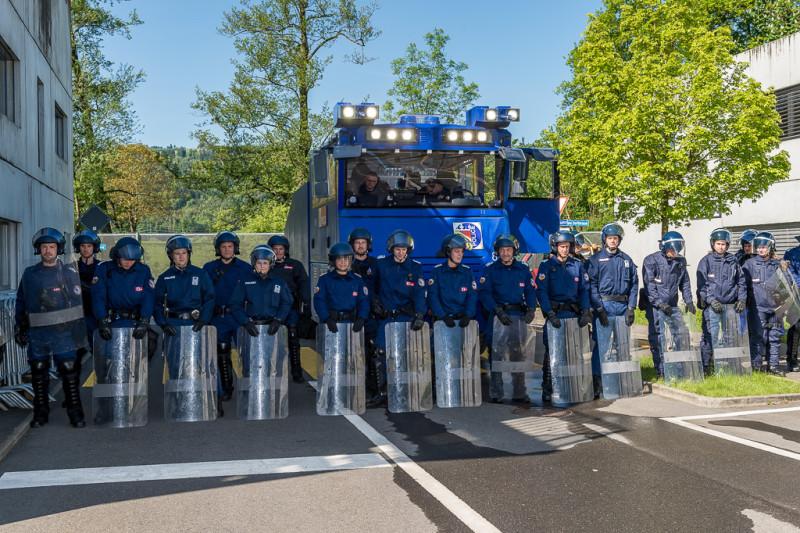 Das Bild zeigt eine Reihe Polizisten mit Schutzhelmen und Schildern, die vor einem gepanzerten Fahrzeug stehen. Dies dient zur Vorführung eines Einsatzes bei einer unbewilligten Demonstration.