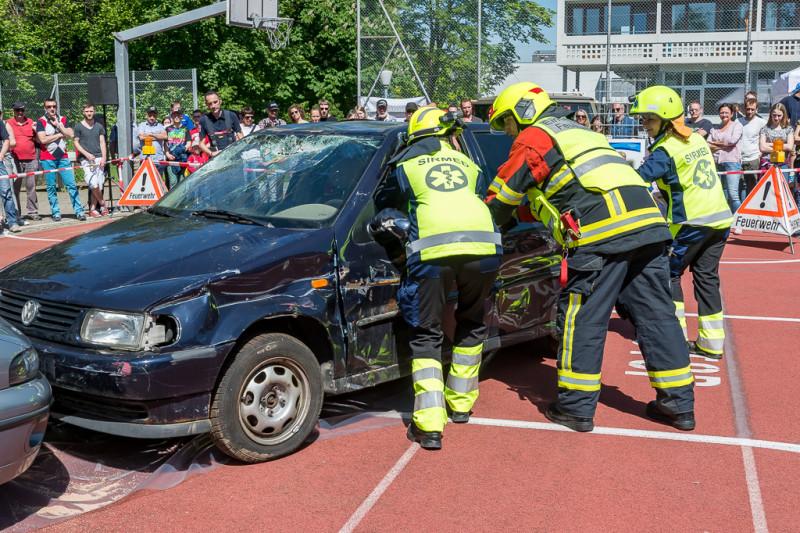 Das Bild zeigt ein Auto, das durch einen Unfall beschädigt wurde. Der Fahrer ist eingeklemmt. Sanität und Feuerwehr müssen zusammenarbeiten, um ihn zu befreien. Die Besucher schauen der Demonstration gespannt zu.