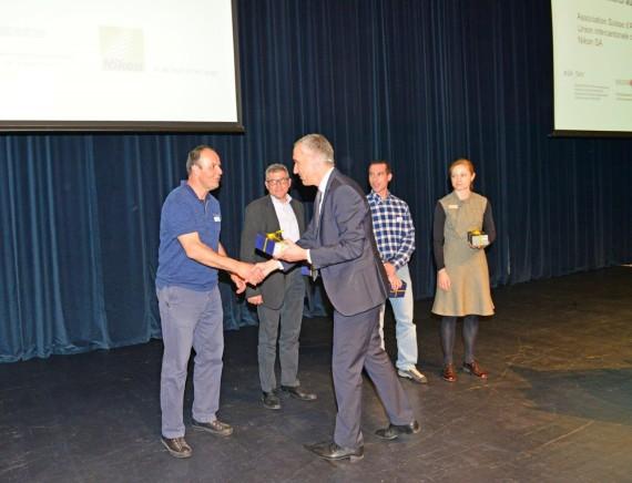 Das Bild zeigt die vier Referenten in einer Reihe. Bruno Spicher schüttelt einem Referenten die Hand und überreicht ihm ein Geschenk.