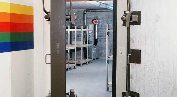 Das Bild zeigt den Blick aus dem Eingang in eine Schutzanlage. Die Panzertüre ist leicht geöffnet. Im Inneren des Raums sind Betten zu erkennen.
