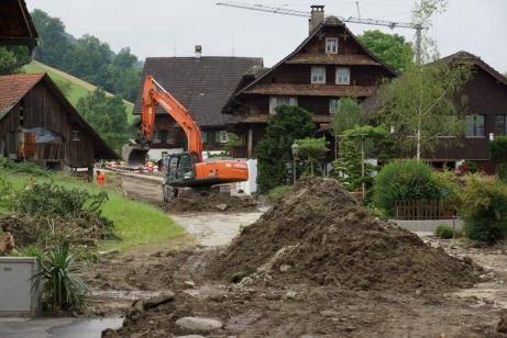 La photo montre le village de Dierikon en août 2015. À l'arrière-plan, on peut voir une grue et une tractopelle à côté d'un grand tas de boue. La route est toujours inondée et couverte de boue.