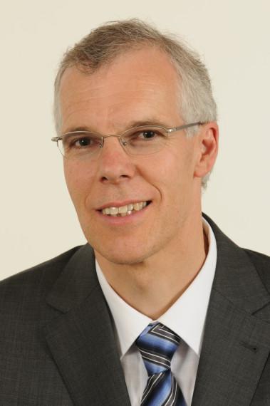 Das Bild ist ein Portraitfoto von Peter Wüthrich. Er hat braune und graue Haare, ein ovales Gesicht und trägt eine Brille mit feinem Rahmen. Er lächelt. Er trägt ein weisses Hemd, eine gestreifte, blaue und graue Kravatte und ein graues Jackett. Der Hintergrund des Bildes ist hellgrau.