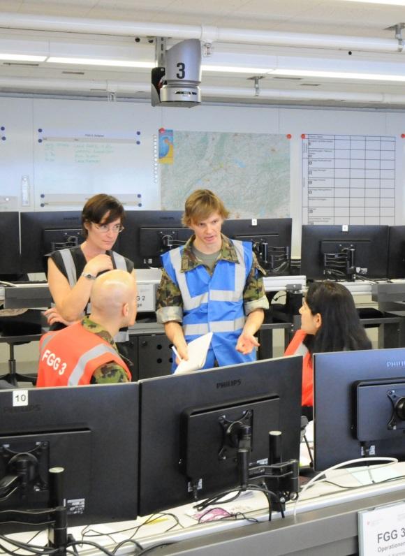 Auf dem Bild sind zwei Männer und zwei Frauen zu sehen. Sie diskutieren etwas. Die beiden Männer tragen Militäruniform. Alle vier sind mit leuchtenden Gilets ausgestattet. Sie befinden sich in einem Raum mit Karten an den Wänden und Computer-Arbeitsstationen.