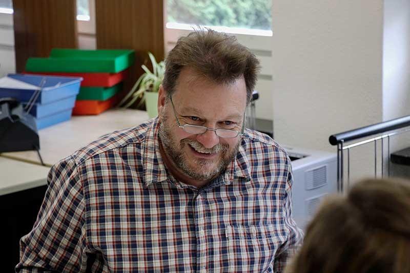 Eric Herbertz, travailleur social et chef du service social pour les sourds de la région bâloise s'entretient avec Pierina Bossert, stagiaire universitaire à la Section Communication de l'Office fédéral de la protection de la population (OFPP). Il est vêtu d'une chemise à carreaux, porte une barbe grise et des lunettes. Il sourit.