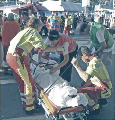 Das Bild zeigt einen Schadenplatz während einer Übung. Vorne in der Mitte liegt ein Mann in einem weissen Tuch eingewickelt auf einer Trage. Um ihn herum stehen 4 Helfer von Sanität und Feuerwehr und binden ihn an der Liege fest. Im Hintergrund sind weitere Angehörige der Blaulichtorganisationen aktiv.