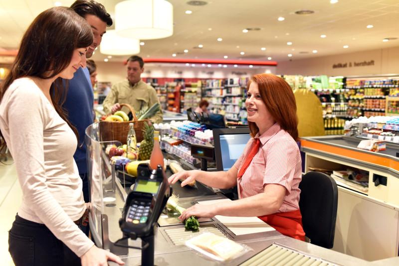 Das Bild zeigt eine typische Kassensituation im Alltag mit Strom. Eine Kassierin mit roten Haaren und in Uniform liest Produkte ein. Ein junges Paar lächelt, sie steht beim elektronischen Kartenleser und wartet darauf, zu zahlen. Im Hintergrund stehen weitere Personen Schlange. Die Regale sind gefüllt und die Lampen eingeschaltet, die Kasse funktioniert.