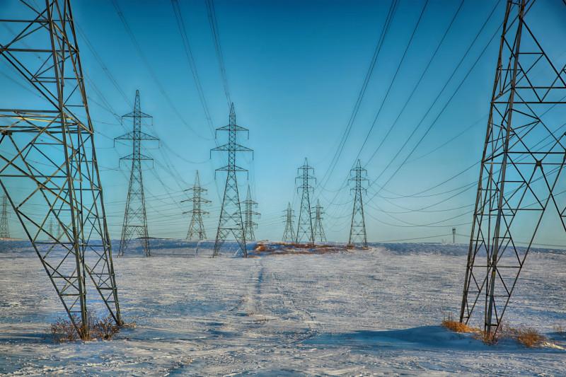 Das Bild zeigt mehrere hintereinander aufgereihte Strommasten und Stromleitungen. Der Himmel ist blau, der Boden weiss oder grau, was auf gefrorenen Boden hindeutet.