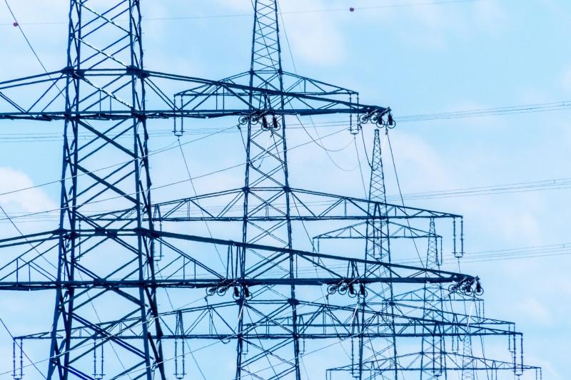 Das Foto zeigt hintereinander mehrere Strommasten und Stromleitungen. Der Himmel dahinter ist hellblau.
