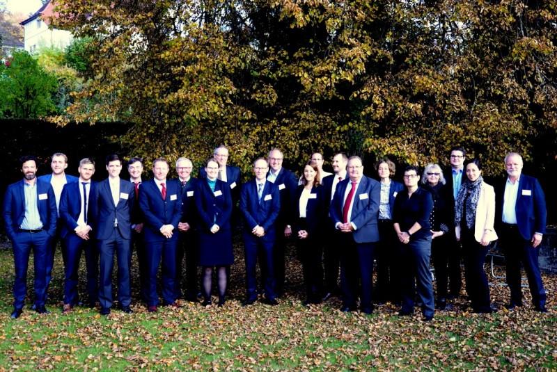 21 Personen stehen in der Reihe aufgestellt und lächeln für das Foto. Sie sind geschäftstauglich gekleidet, grösstenteils in dunkelblauen Anzügen. Sie stehen auf einer Wiese vor einem Baum.