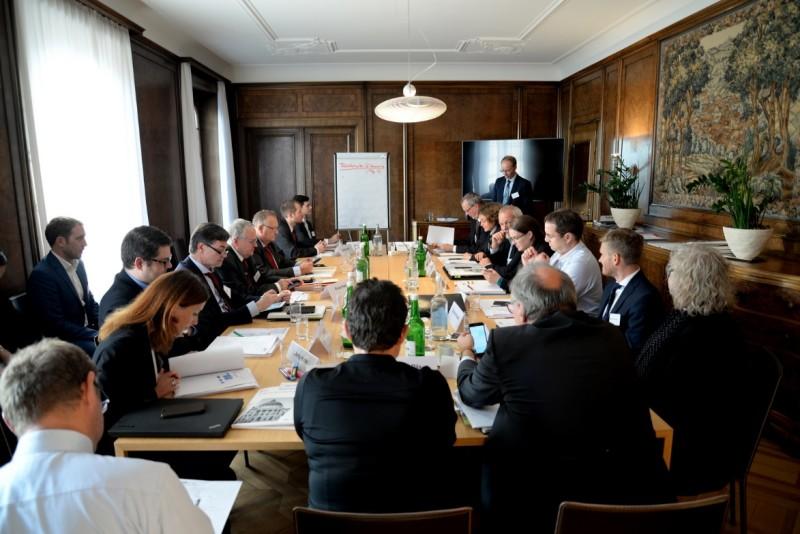 In einem Raum sitzen ungefähr 20 Personen um einen langen Tisch. Vorne steht ein Mann, der an einer Tafel etwas präsentiert. Die Zuhörenden machen teilweise Notizen und hören scheinbar gespannt zu.