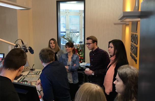 Sechs Lernende schauen einem Radiomacher zu, wie er am Mischpult arbeitet.
