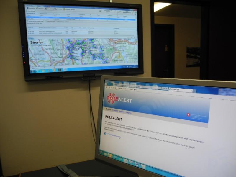 Das Bild zeigt zwei Bildschirme: Einen Laptop- und einen Fernsehbildschirm. Auf dem Laptop wird gerade die Funktion «Polyalert starten» ausgewählt. Auf dem Fernseher kann auf einer Karte der Schweiz gesehen werden, welche Sirenen gerade heulen.